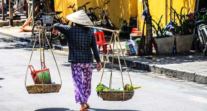 woman with traditional gear walking on street in hoi an ancient town, vietnam